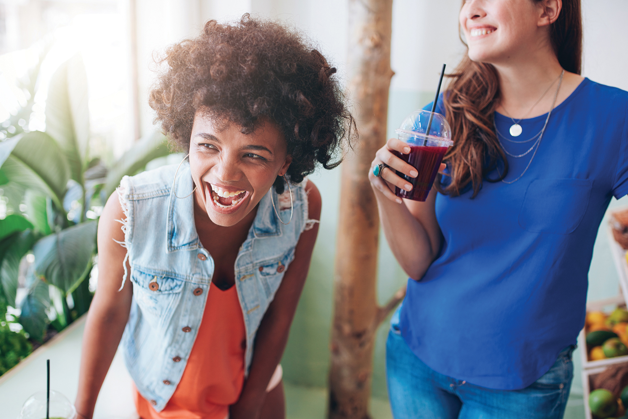 Two women laugh while drinking cold pressed juice